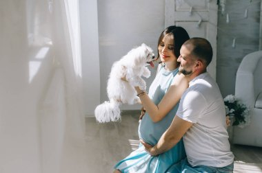 Young happy couple expecting baby standing together indoors