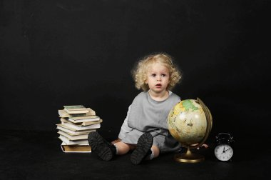 Happy little girl with a books, globe and clock on a black background