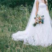 Nevěsta ve svatebních šatech s svatební kyticí v ruce