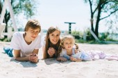 Happy family outdoors spending time together. Father, mother and daughter have a fun and playing on a beach