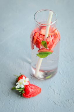 Fresh orange, strauberries, mint with water in bottles.