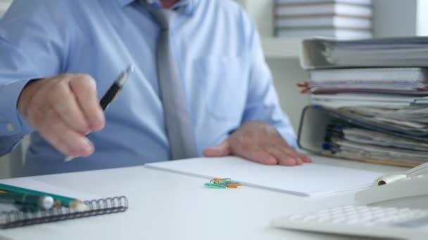 Businessman in Office Room Writing in Accounting Documents Using a Pen