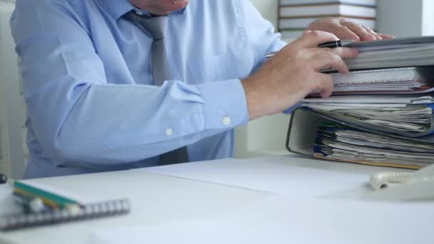Businessman in Office Room Counting Files and Documents Writing on a Paper