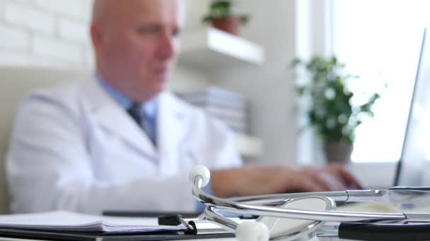 Stethoskop im fokussierten Bild und ein Arzt mit Laptop im unscharfen Hintergrund