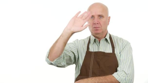 Mitarbeiter mit Schürze bleiben ernst und machen Hallo-Gesten oder grüßen Handzeichen