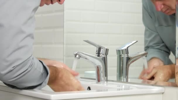 Tired Man in Bathroom Washing His Face with Fresh Water from Sink Faucet