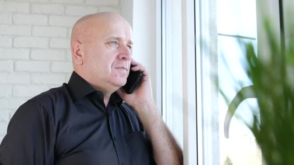 Businessman in Office Room Talk Using Mobile Gesturing and Looking on the Window