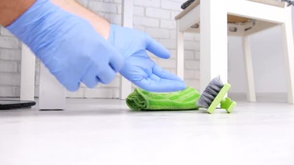 Dělník čištění podlahy s čisticím prostředkem pomocí štětce a barevné ochranné rukavice