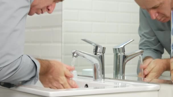 Man in Bathroom Washing Face and Hands in Sink with Chill Water from Faucet