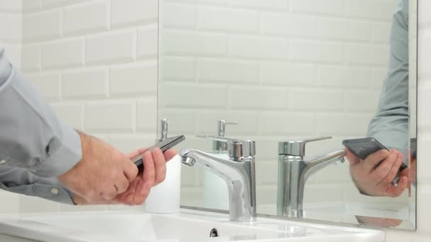 Businessperson in Bathroom Leave Cellphone and Wash His Hands with Water