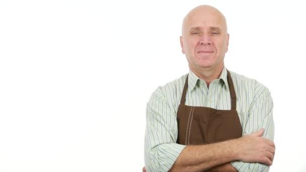 Mann mit Küchenschürze lächelt und macht Handgesten