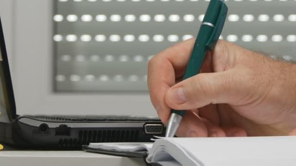 Zavřít se podnikatel práce v kanceláři psát v agendě a typ dat v notebooku