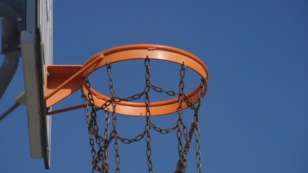 beliebtes Spiel in Zeitlupe Schießen mit Ball fällt in Basketballkorb