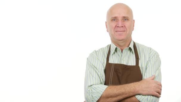 Mann trägt Küchenschürze Lächeln und Hallo Gesten mit Hand grüßen