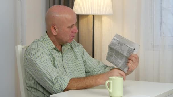 Muž si vychutnat šálek kávy v obývacím pokoji čtení novin