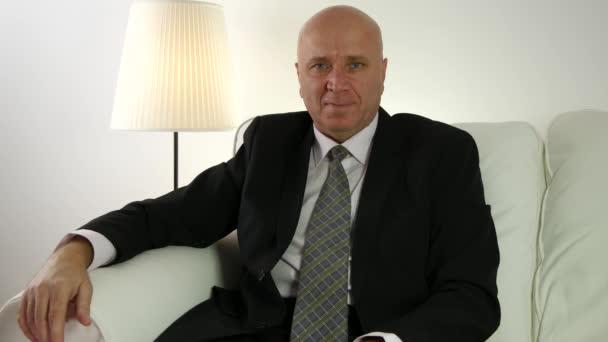 Geschäftsmann im Bürogebäude setzt sich auf Sofa und grüßt mit Hallo-Handgesten