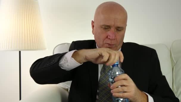 Žíznivý podnikatel uvnitř Office místnost pití pitné vody z plastové láhve