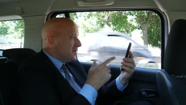 Nadšený podnikatel cestující s Taxi Cab číst dobrou zprávou na mobilní telefon