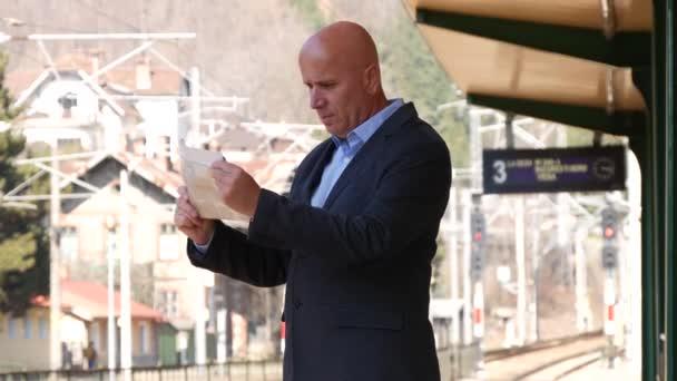 Podnikatel, čeká vlak příjezdy číst noviny procházení stránek Gazette