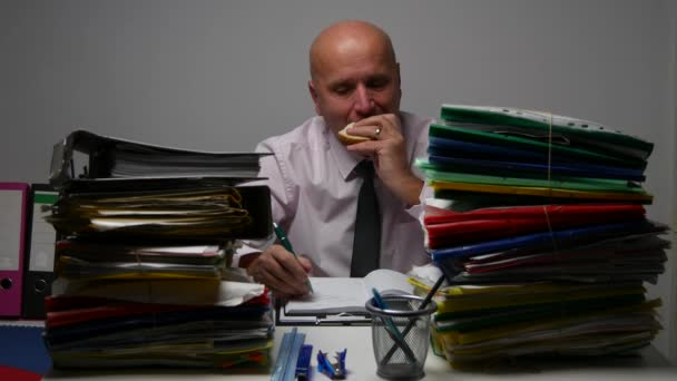 Office Archive Starved Businessman Eating a Sandwich and Write in Agenda Work.