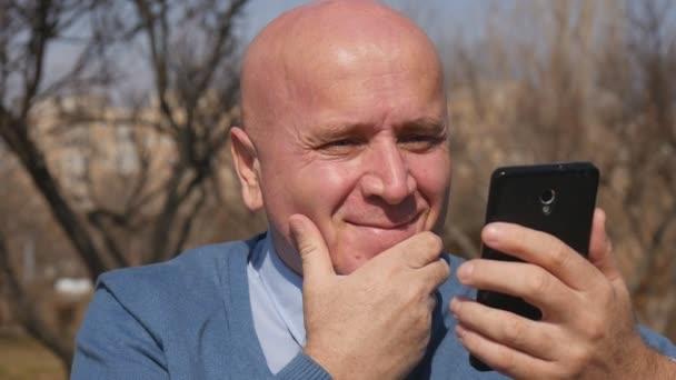 Šťastný podnikatel ukázal dobrou zprávou mobilních zpráv zpomalené zobrazení pro čtení