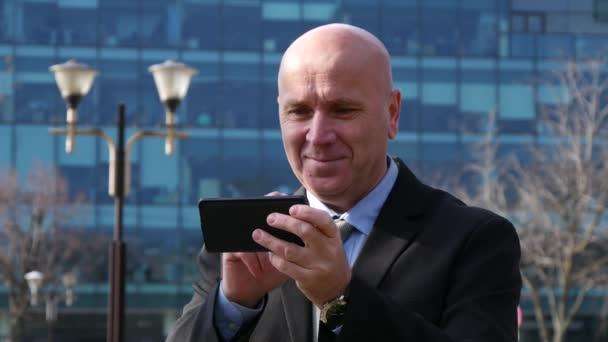 Podnikatel čtení vzrušující dobrou zprávou na mobilní telefon Email ukázal šťastný