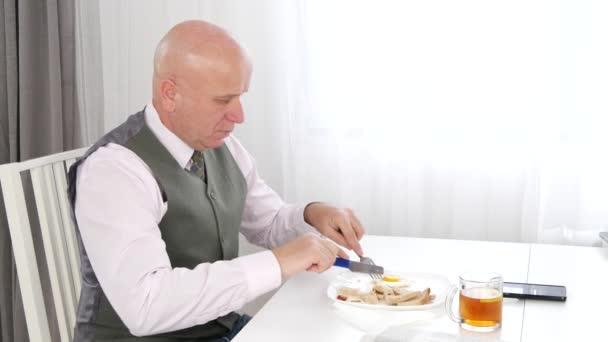 Pohledný podnikatel v restauraci při snídani a čtení noviny