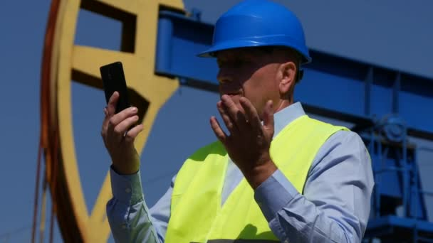 Oil Pump Engineer Using Mobile Internet for Video Call with Maintenance Team
