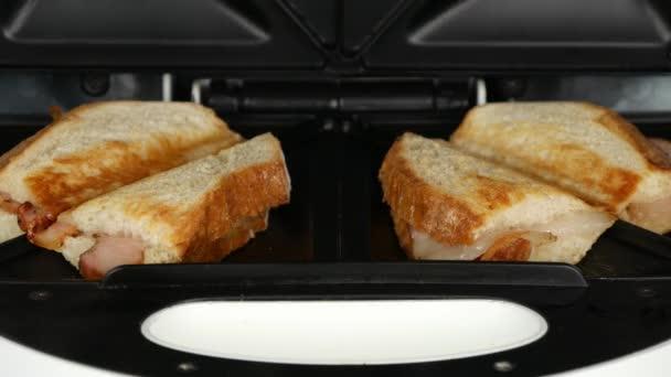 Detailní záběr rukama člověka otevírání připravuje dva slaninou sendviče sendvičovač