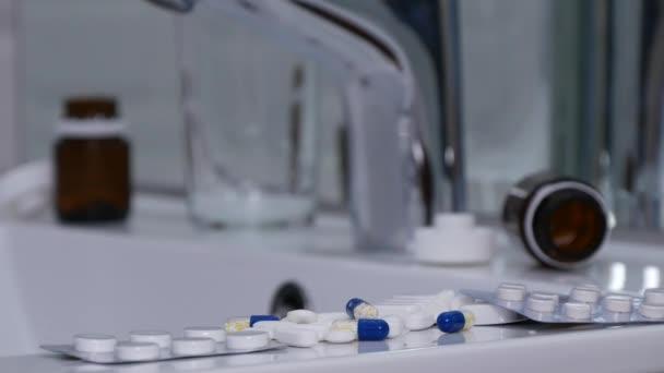Trpící člověk v koupelně vzít prášky s sklenici s vodou