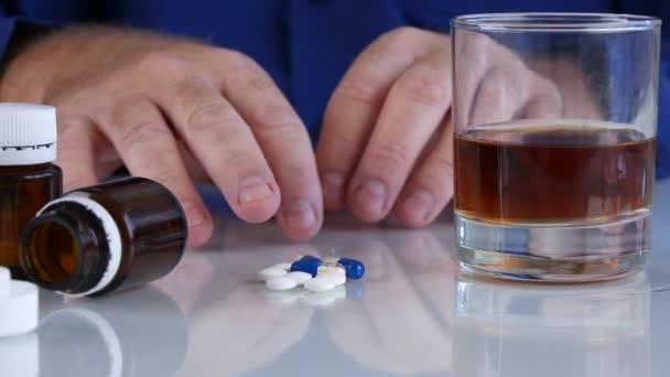 Süchtiger Mann mit Händeschütteln nimmt Tabletten vom Tisch
