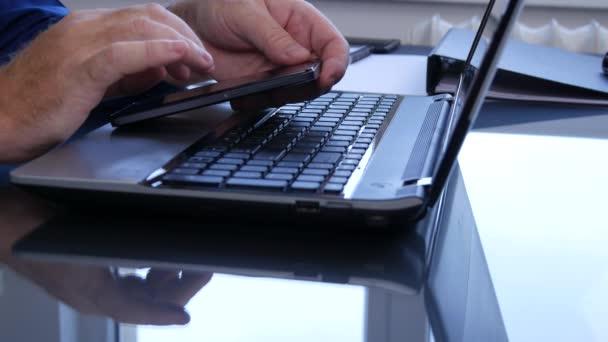 Geschäftsmann arbeitet im Büro mit drahtloser Verbindung von Smartphone und Laptop