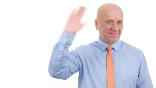 Jistý podnikatel úsměv při pohledu na fotoaparát a gesta rukou, aby Hello