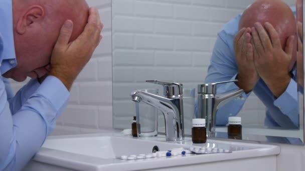 Člověka, který trpí velkou bolestí hlavy před zrcadlo do koupelny