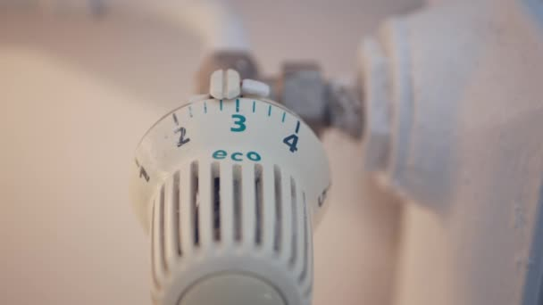 Man in Office Room Setting Radiator Temperature from Thermostat Saving Energy