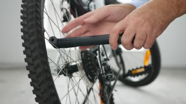 Střelba s mužem vhánění vzduchu v pneumatikách kolo uvnitř sportovní vybavení obchod