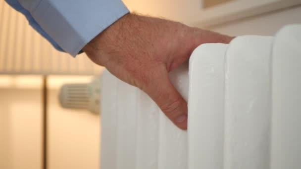 Obrázek muže rukou kontrolu teploty radiátor a nastavení termostatu hodnoty