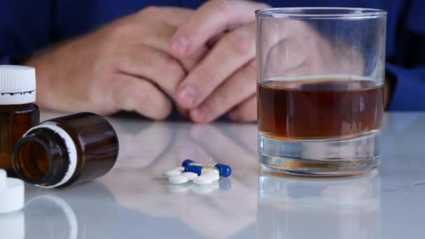 Alkoholiker vor Alkohol und Tabletten beim Händeschütteln