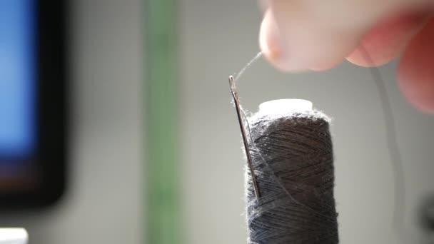Nahaufnahme mit Menschenhand, die einen Faden in ein Nadelloch einführt