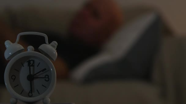 Müde Menschen aufwachen aus Bett und Blick zum Wecker in der Mitte der Nacht