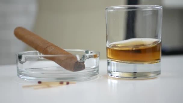 Černý kuřácký doutník v popelníku a sklenička se whisky na stole