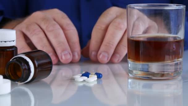 Závislá osoba s rukama třepáním vzít léky z tabulky s alkoholem