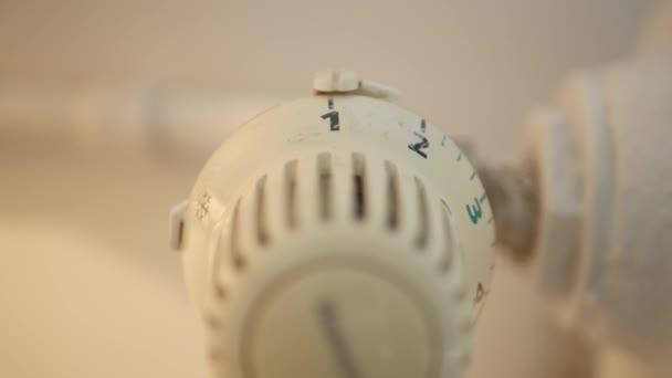 Man Setting Home Radiator Temperature from Thermostat Valve Saving Energy