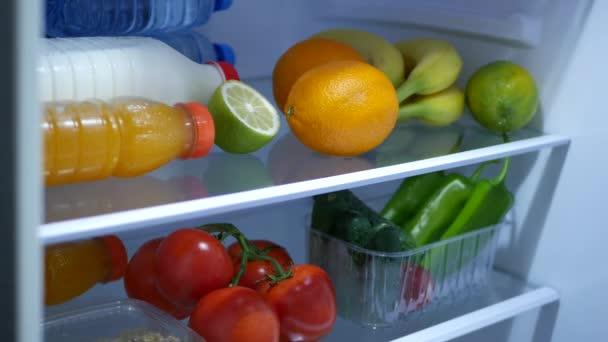 Idős ember kezek nyit új hűtő ajtót, és hogy egy narancs gyümölcs-és friss Juice