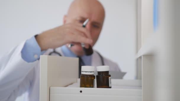 Zeitlupe mit Arzt, der ein Rezept schreibt und in einer Schublade nach Medikamenten sucht