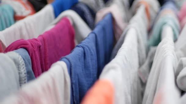 Nasse und saubere Kleidung zum Trocknen auf einem metallischen Träger im Badezimmer