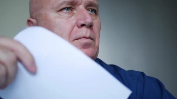 Muž v místnosti, kde je velmi horko, se zvedne pomocí listu papíru a otře si pot z čela