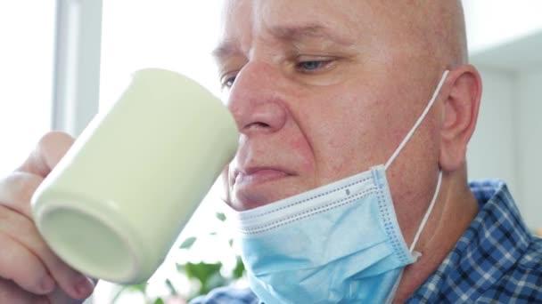 Mann mit OP-Maske im Gesicht trinkt entspannt eine Tasse Kaffee