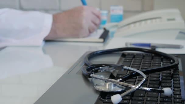 Arzt sucht ein Medikament und verschreibt eine Behandlung, Arzt schreibt ein ärztliches Rezept in der Krankenhaussprechstunde