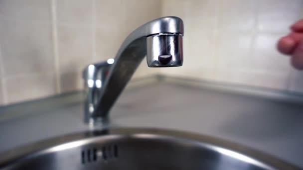 Vrouw opent waterkraan tap water vloeit voort uit kraan keuken